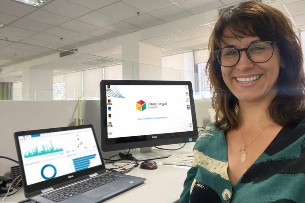 Uma mulher branca e de óculos ao lado de telas de computador