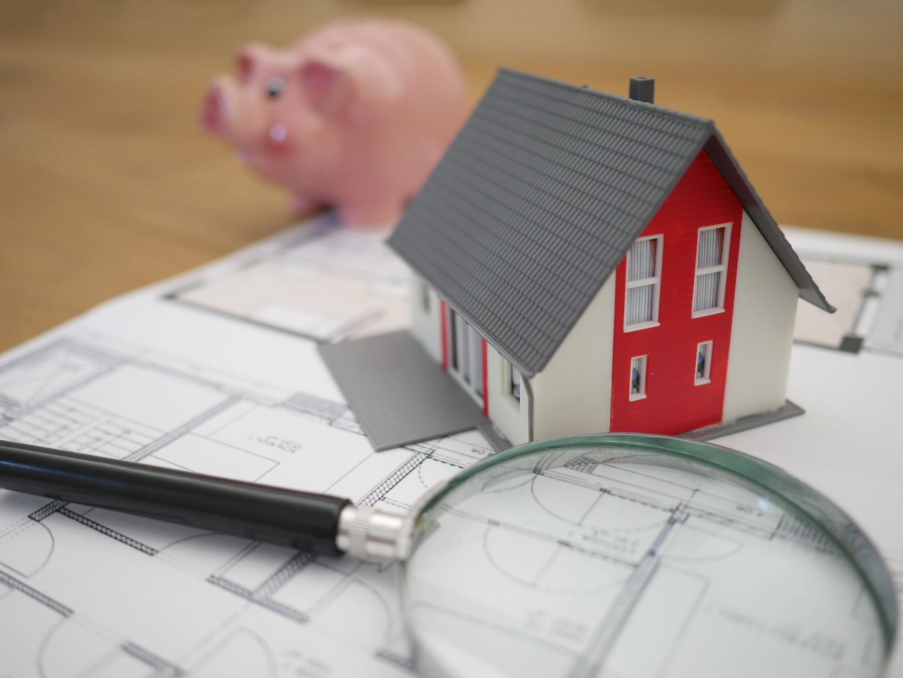 Model home and piggy bank on table