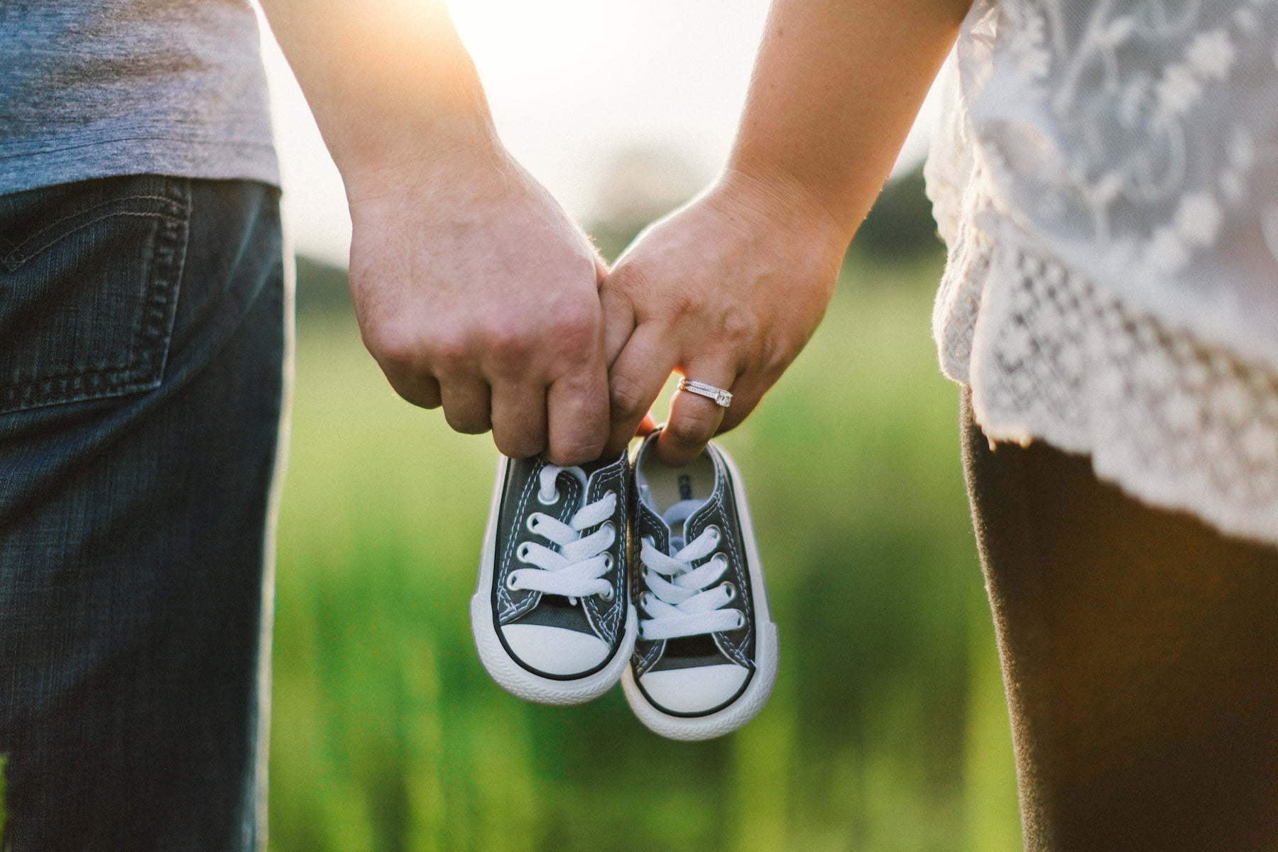 Couple holding hands with baby's shoes