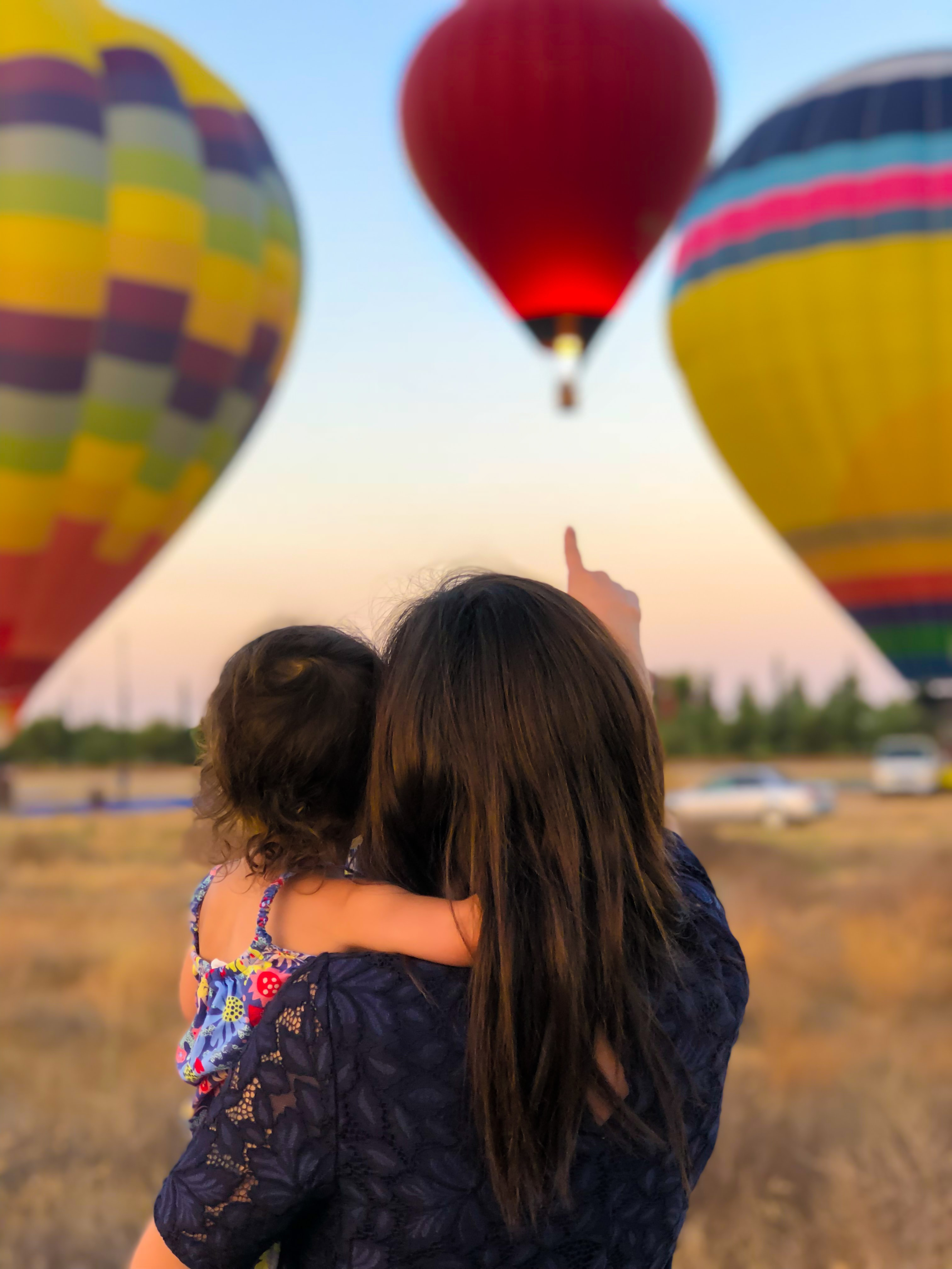 Mother holding daughter and pointing at balloons