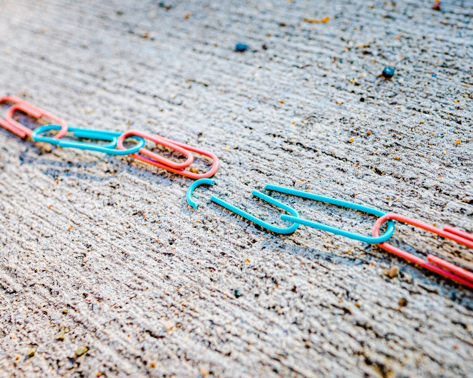 Broken chain of paper clips on stone