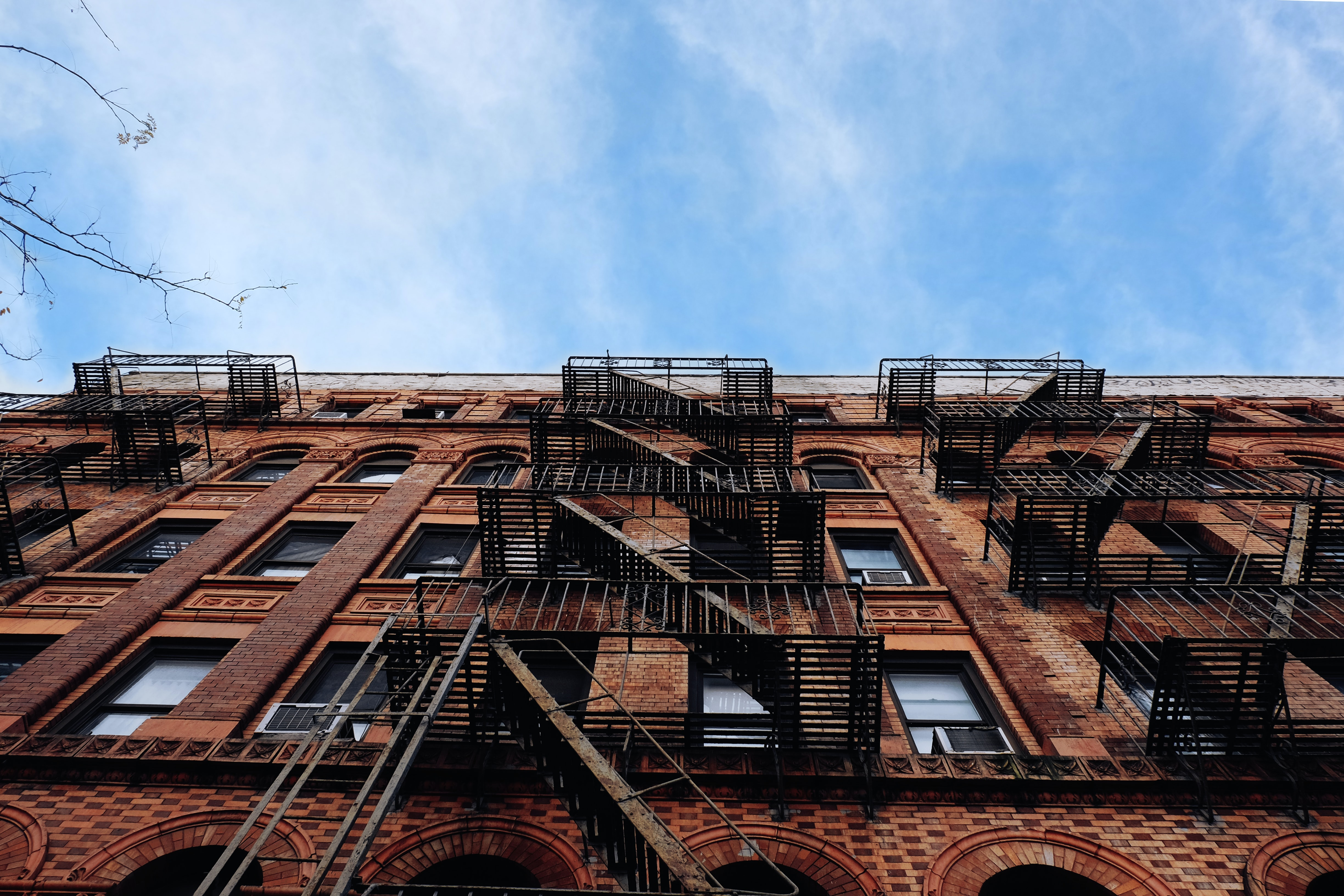 Apartment building with fire escape and blue sky