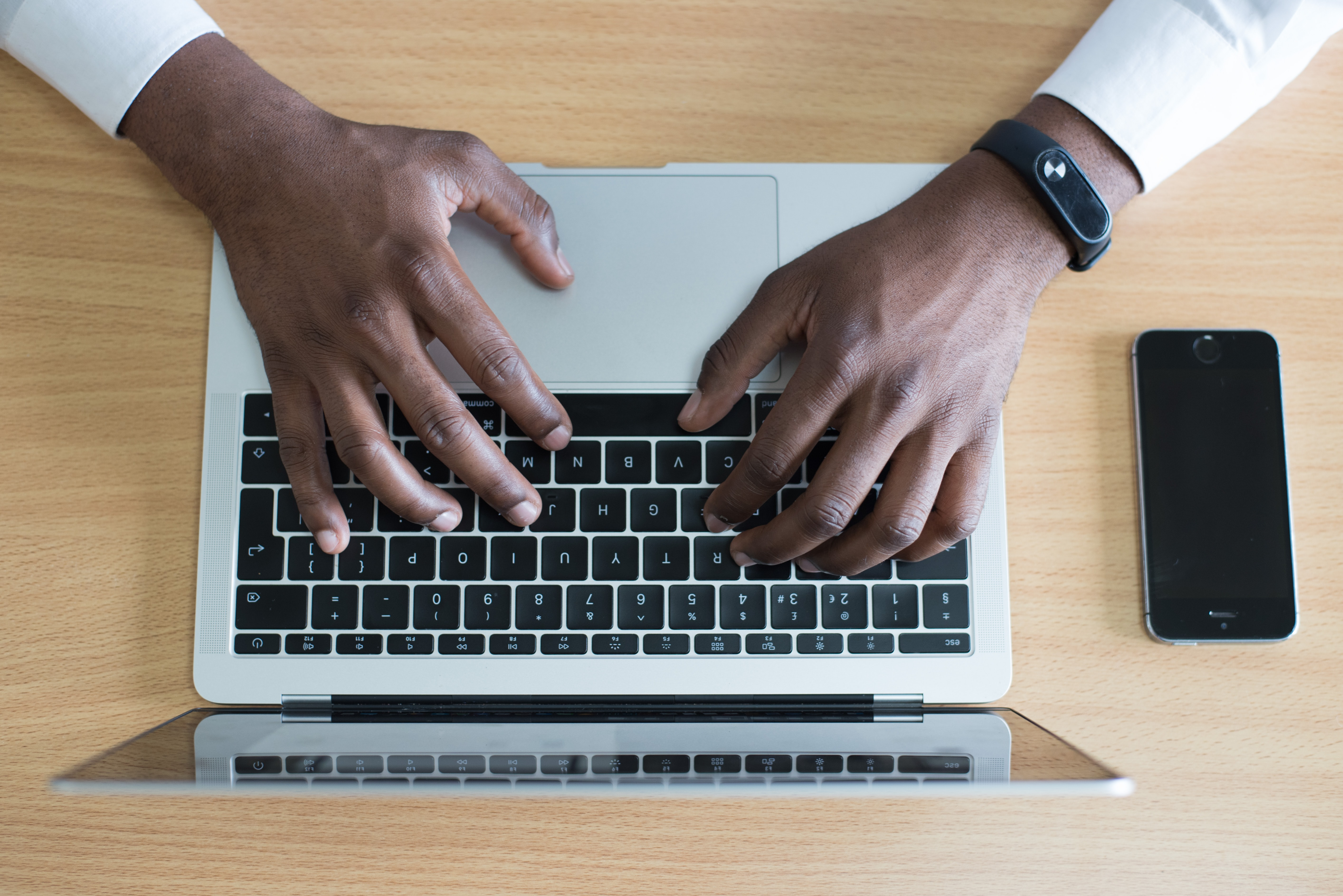 Man's hands on keyboarad making estate plan on computer.