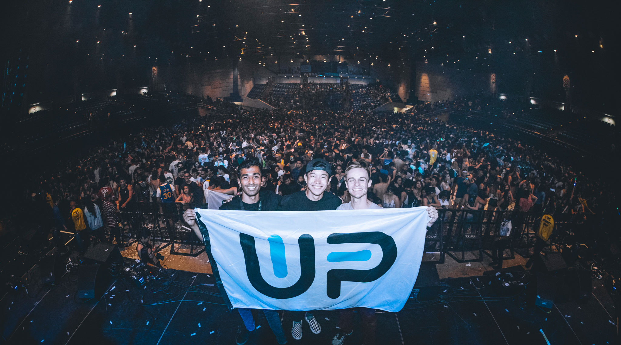 Group of students holding Up & Up flag at concert