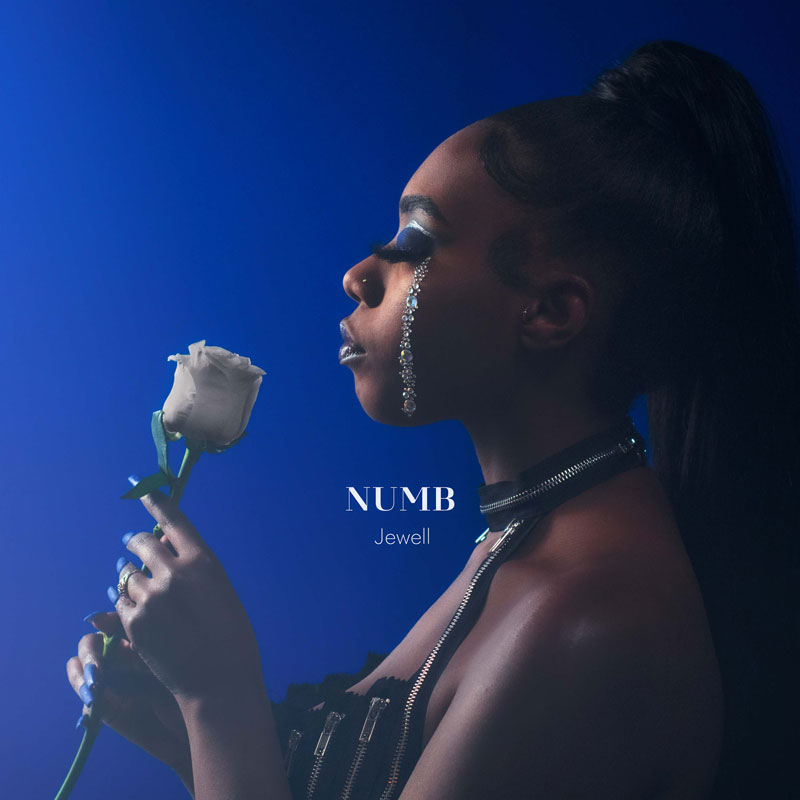 """Album Cover for the single """"numb"""" by Jewell showing the artist on a blue background smelling a white rose with diamonds on her face which look like tears"""