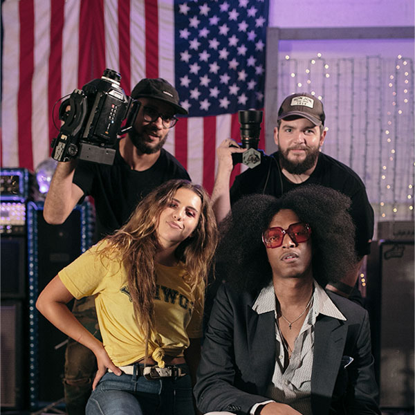 Behind the scenes picture of the video production for Mike Floss by Altru Creative showing the crew of three people and the artist in front of the American flag and some string lights.
