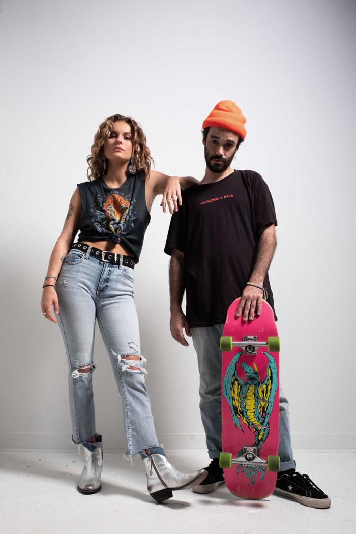 Artist Grey Zeigler standing next to another collaborator in front of a white background with grunge inspired outfits.
