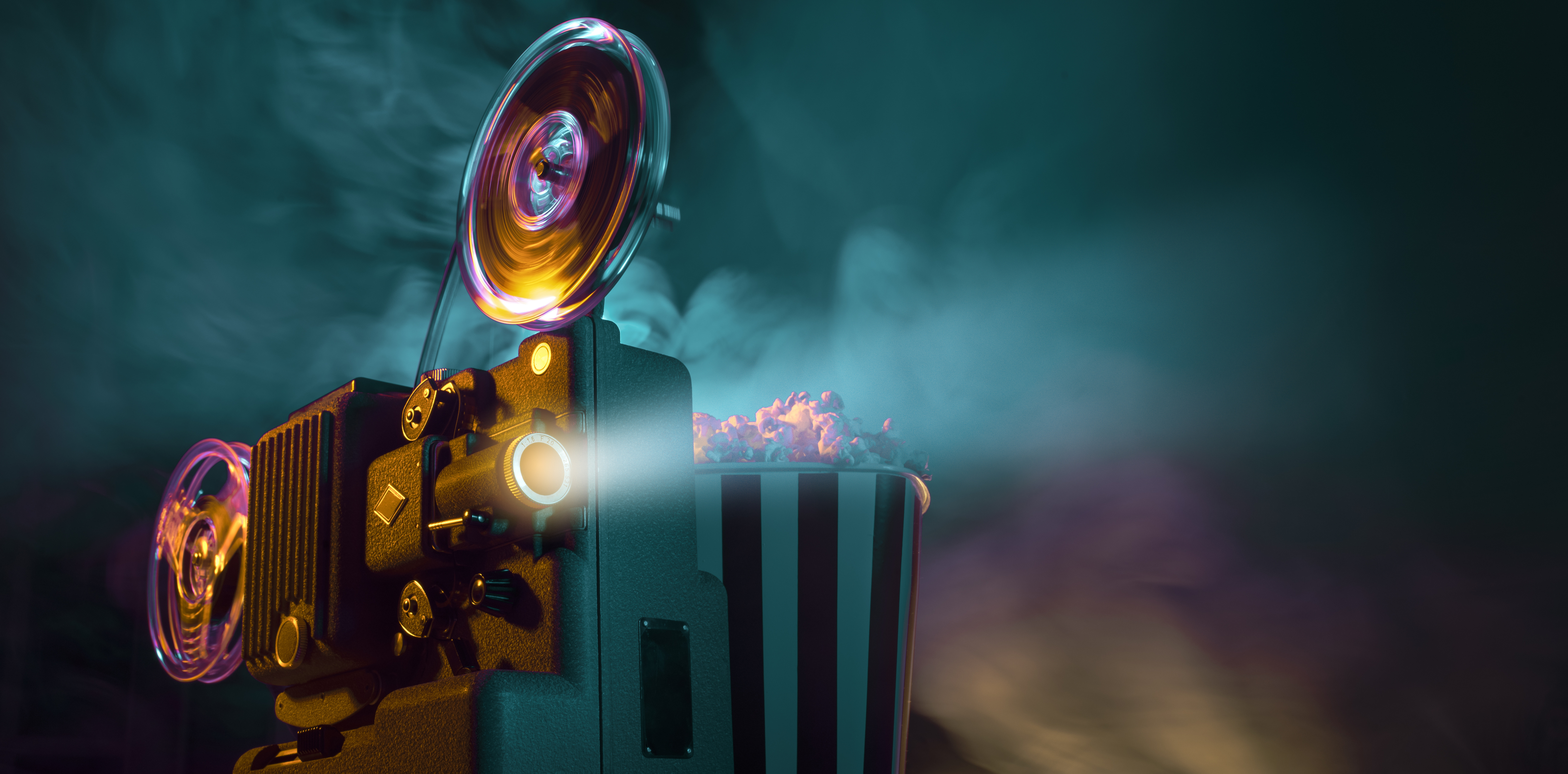 A vintage, neon movie projector is playing with a full popcorn bucket to the right and a light cloud of smoke surrounding it.