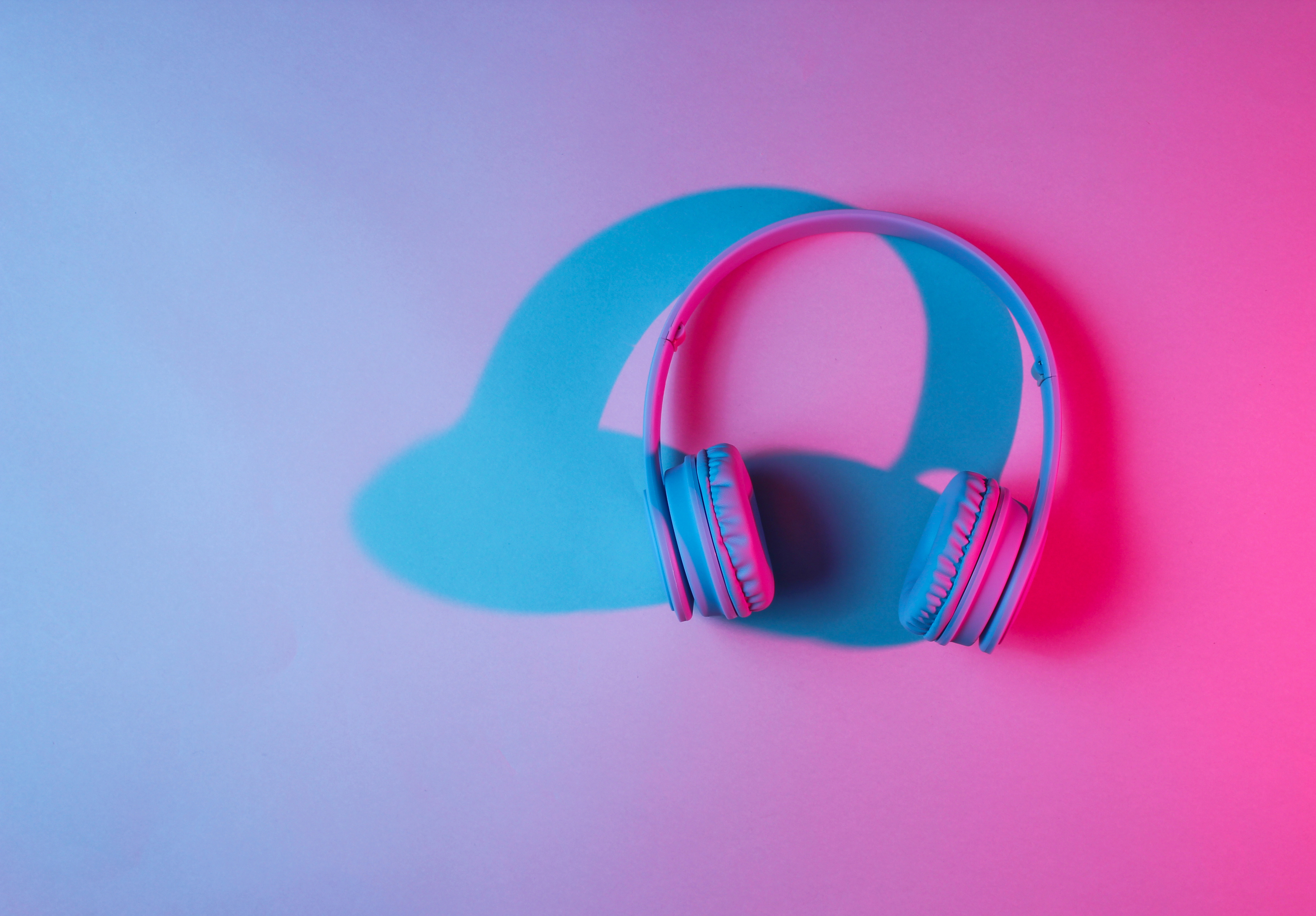 Blue, purple, and pink lights blending together and creating a shadow over a pair of white headphones