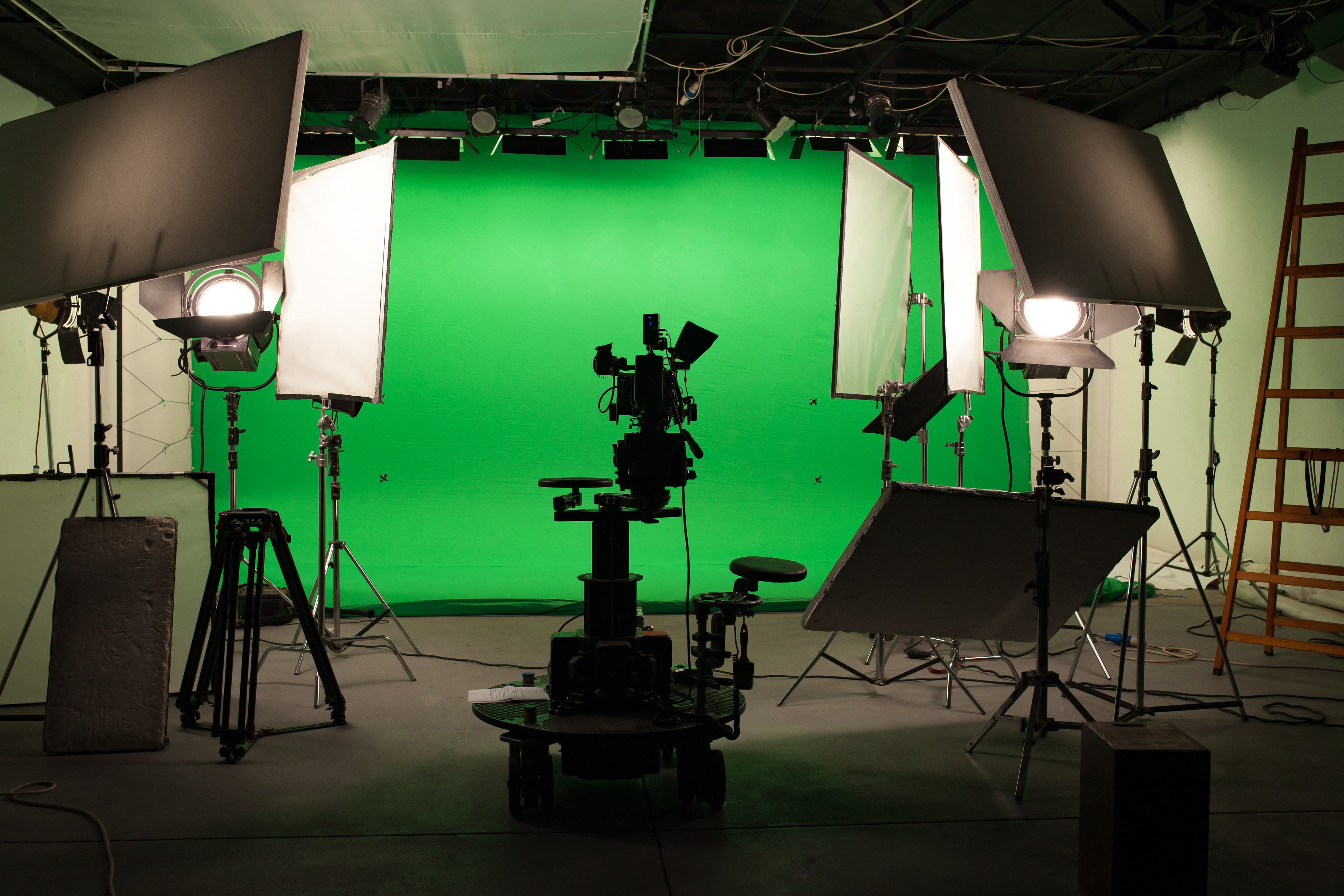 A greenscreen is set up, surrounded by high quality camera equipment and lights