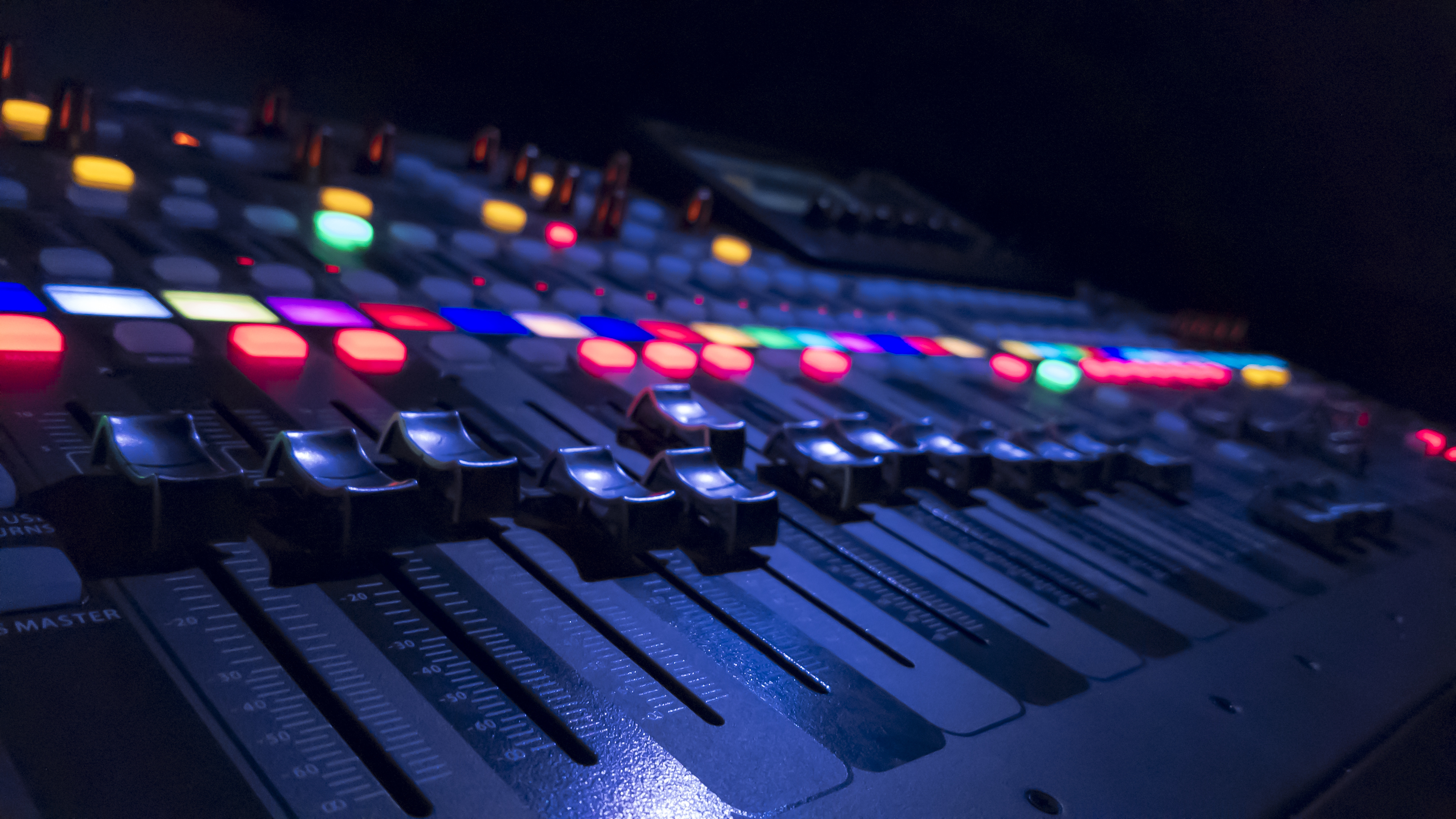 A colorful mixing console in a dark room lit up with bright colors