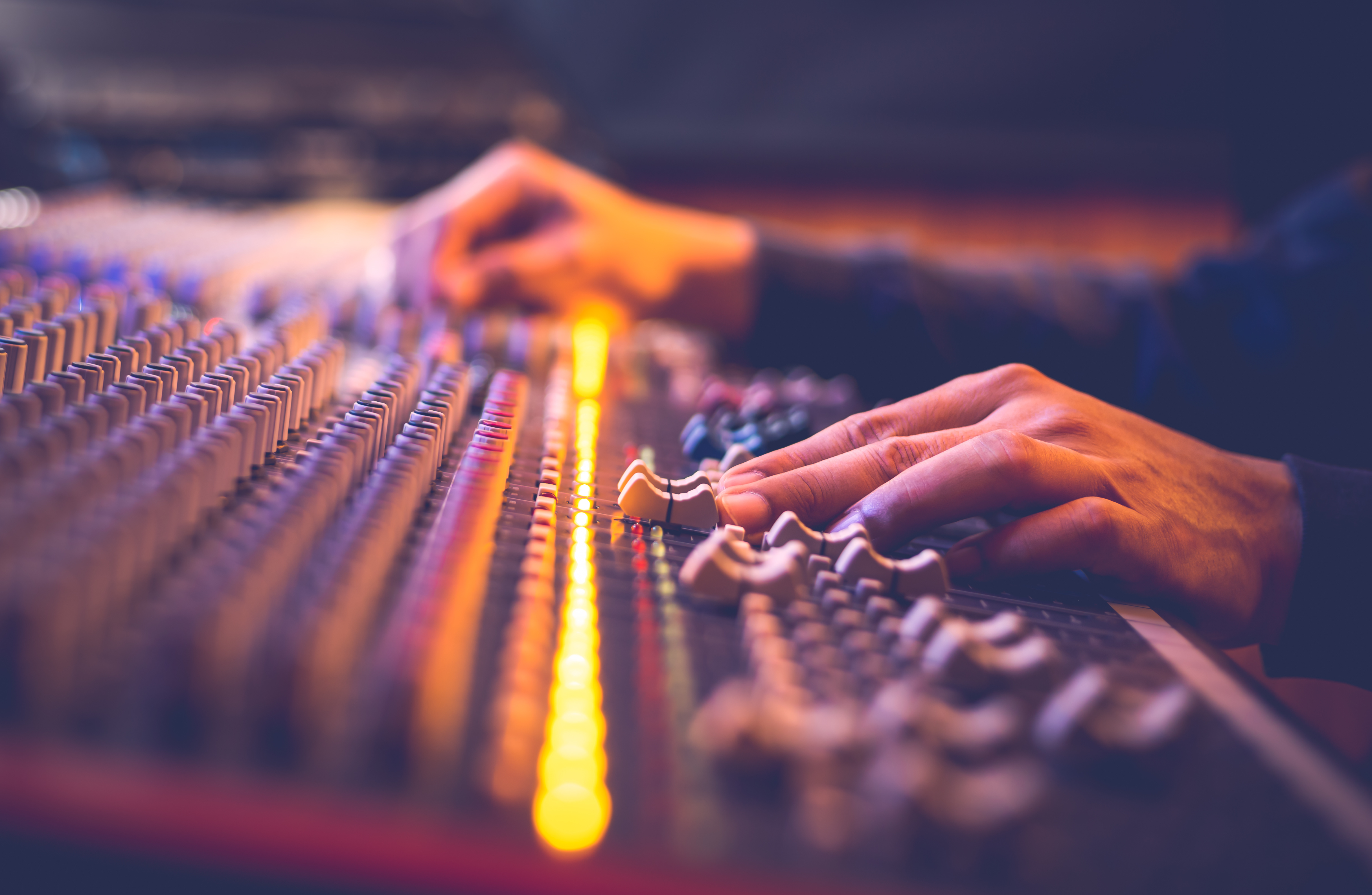 Two hands on a mixing console, sliding levers around during production.