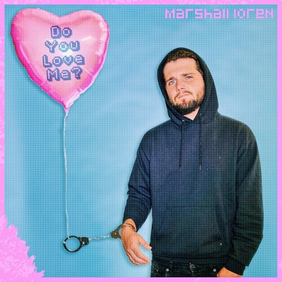 """Marshall Loren holds a pink, heart shaped balloon with the title """"do you love me?"""" printed on it. He is dress in a black hoodie on a blue background with pink on the edges."""