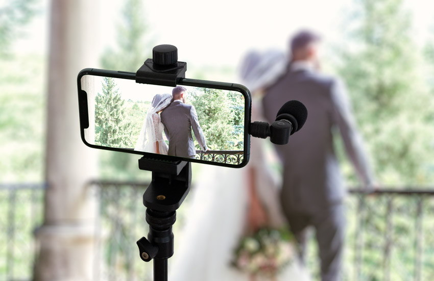 smartphone on tripod with microphone live streaming a wedding