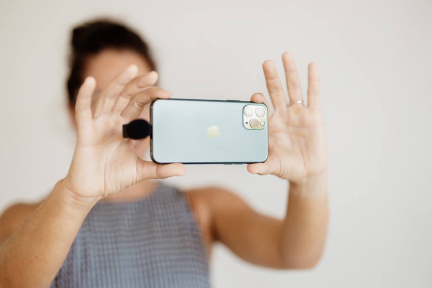 women holding a smartphone while live streaming