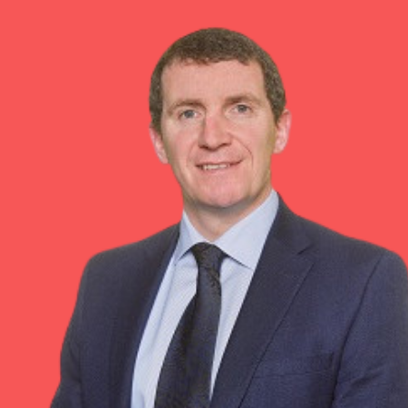 A professional headshot image in colour of Niall Murray, managing director of Collins McNicholas on a red background