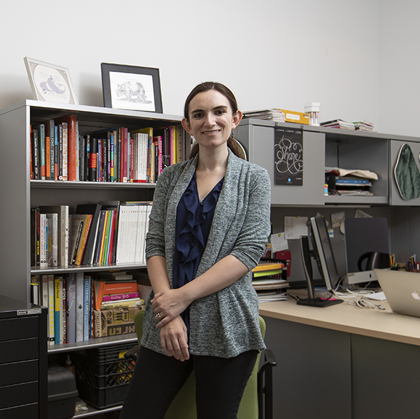 Jenny Kowalski stands in an office with books and art on shelves.