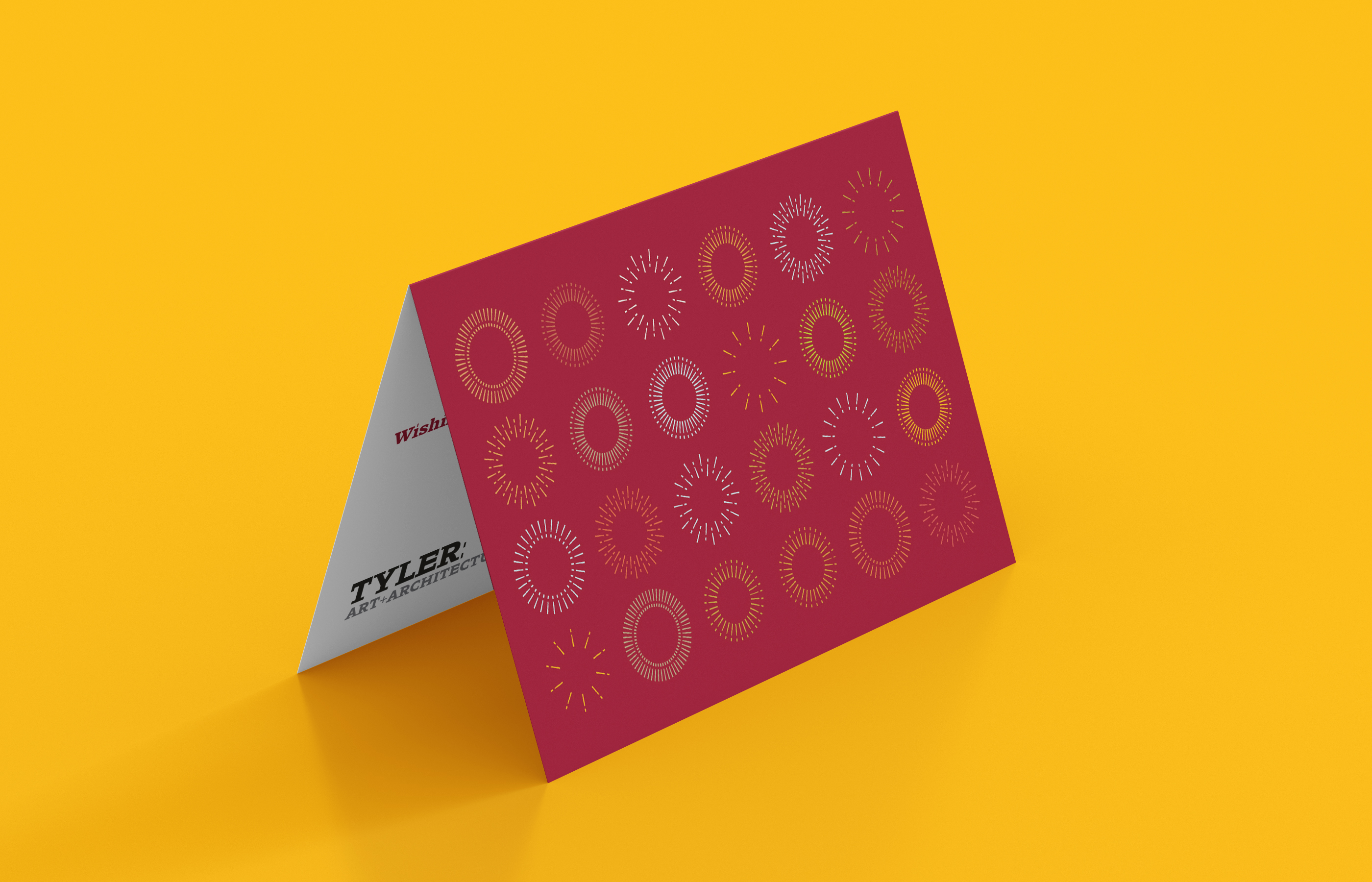 A red folded card on a yellow background features a series of circles made from exclamation points in different colors