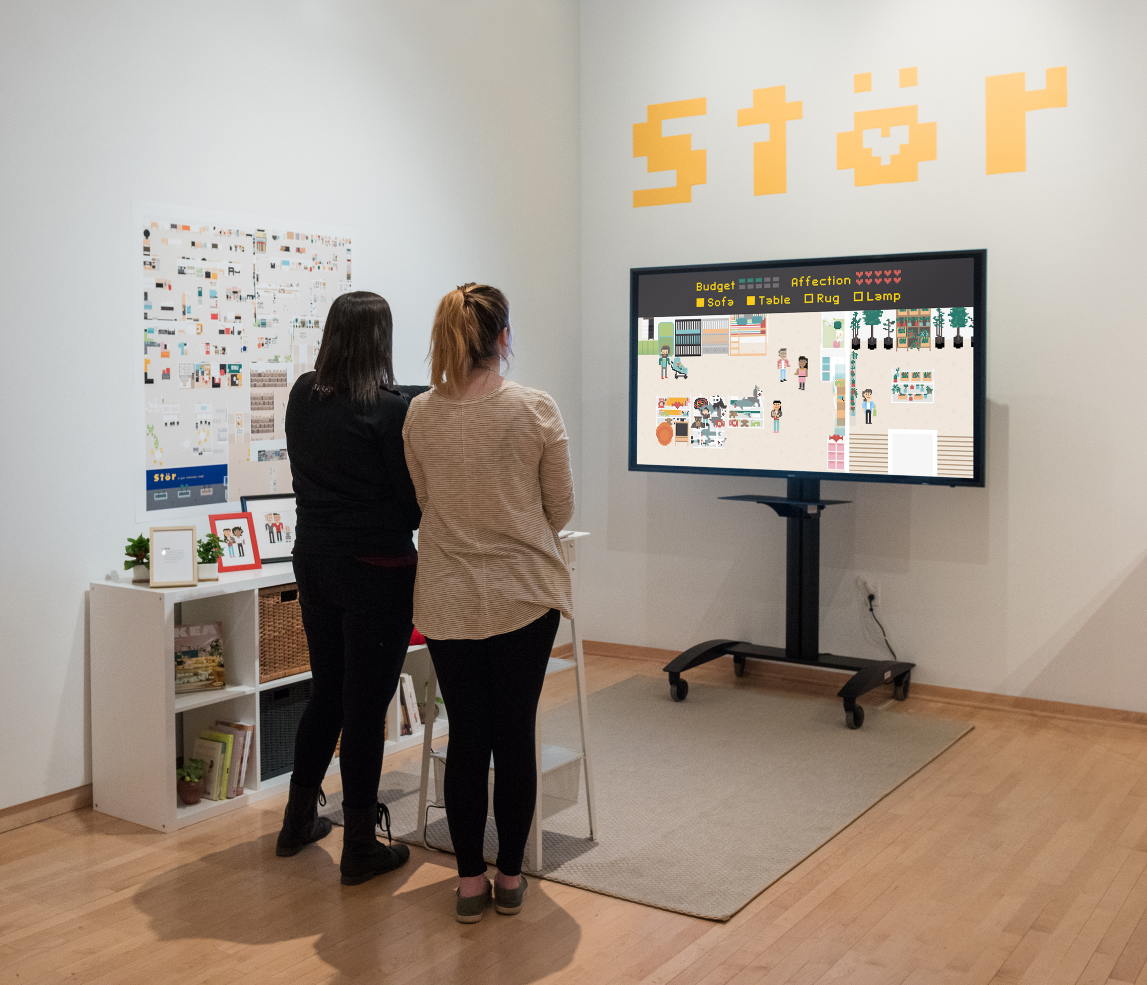 Two women stand in front of a large TV playing the game