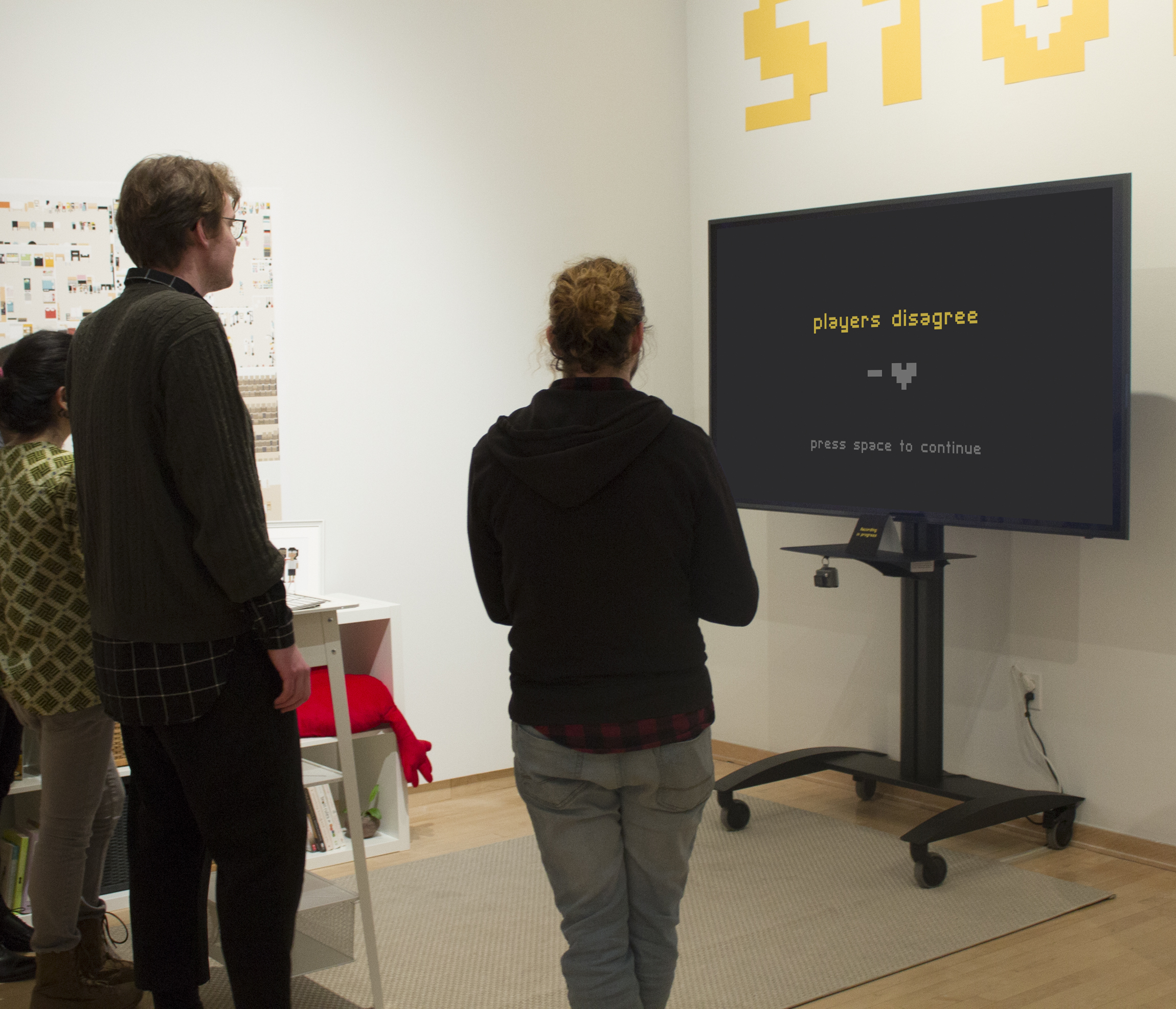 """A group of people stand in front of a large TV with the words, """"players disagree"""" and a minus symbol next to a heart"""