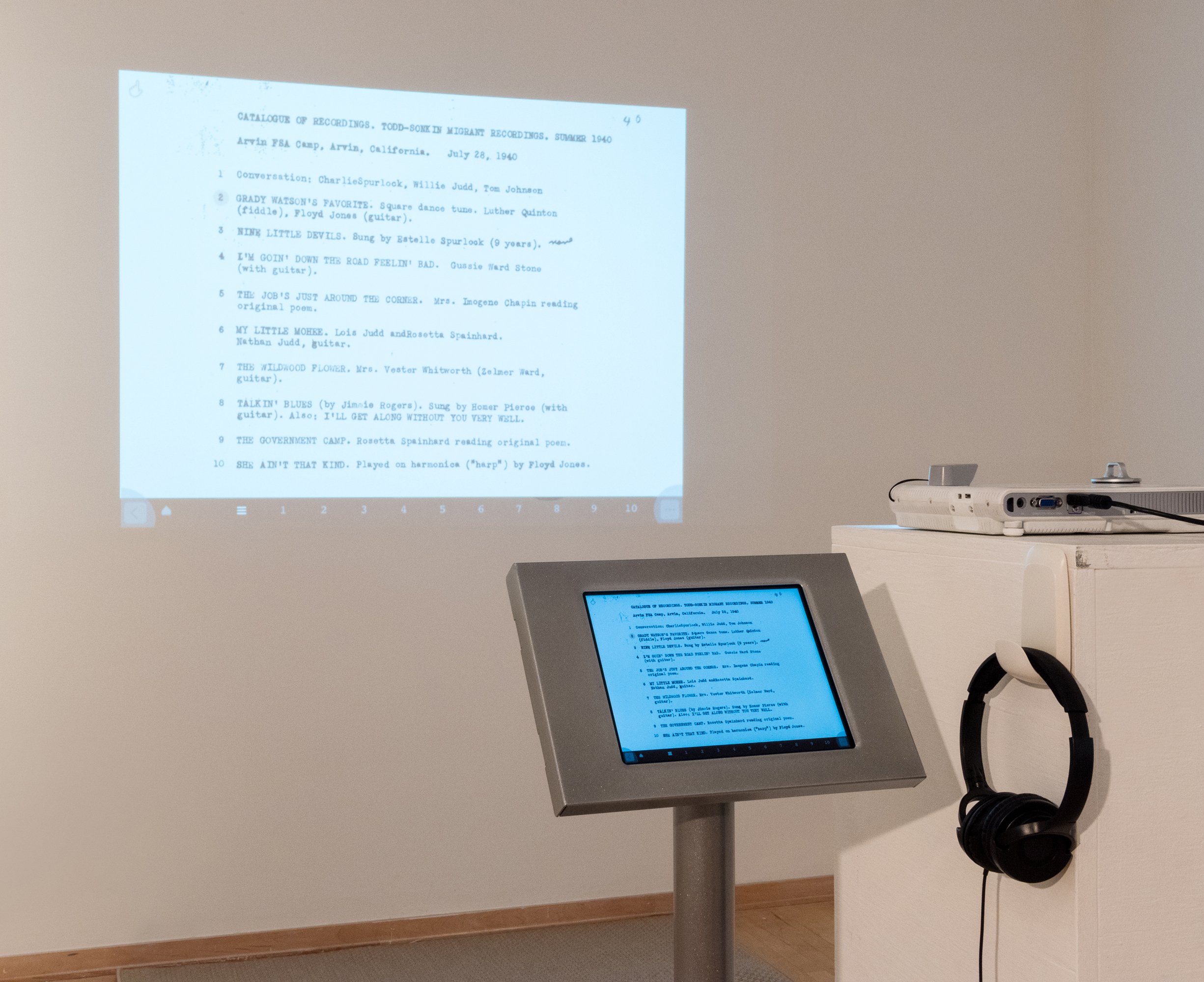 An ipad in a stand and headphones in front of a projected screen