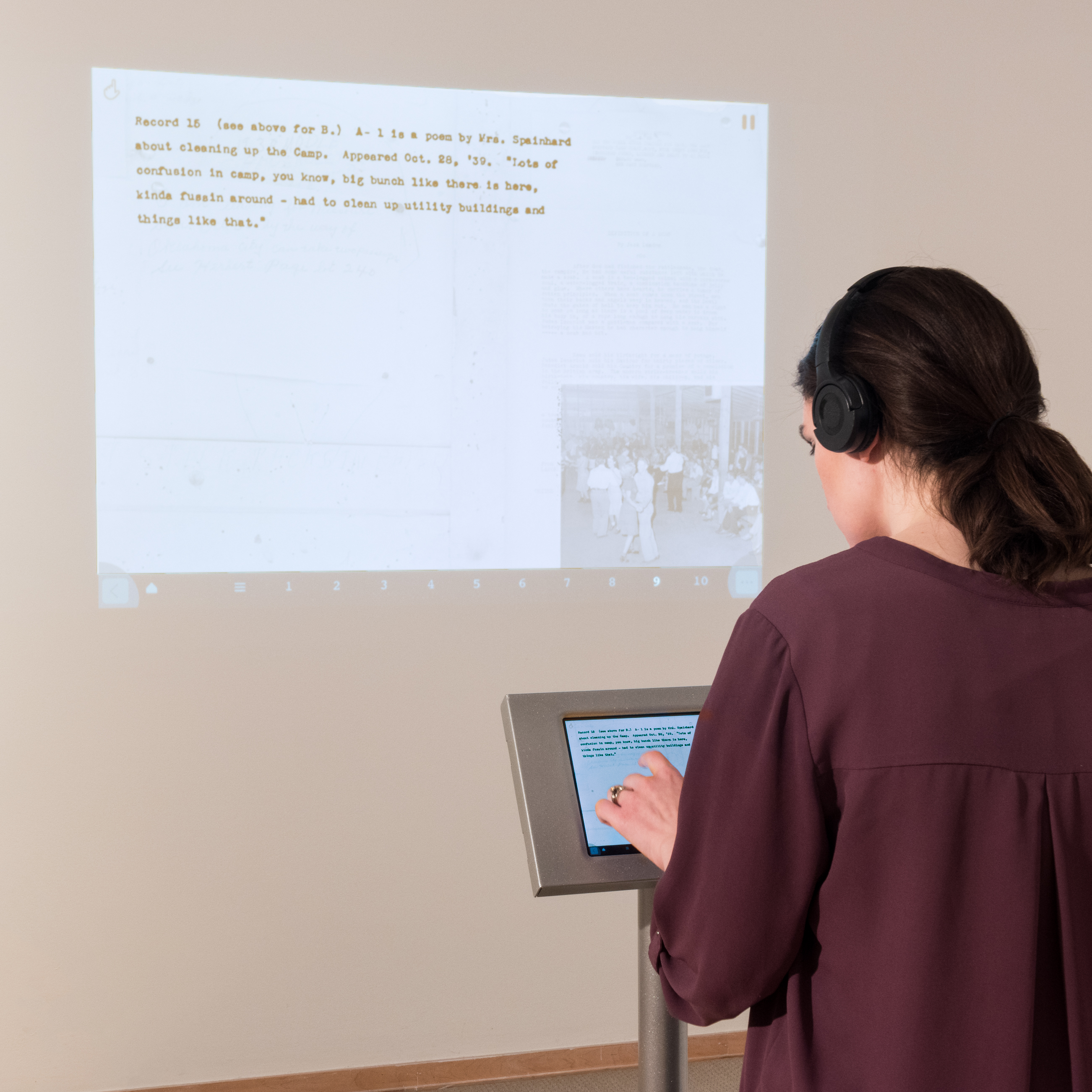 A woman touches a ipad in a stand to control a projected display
