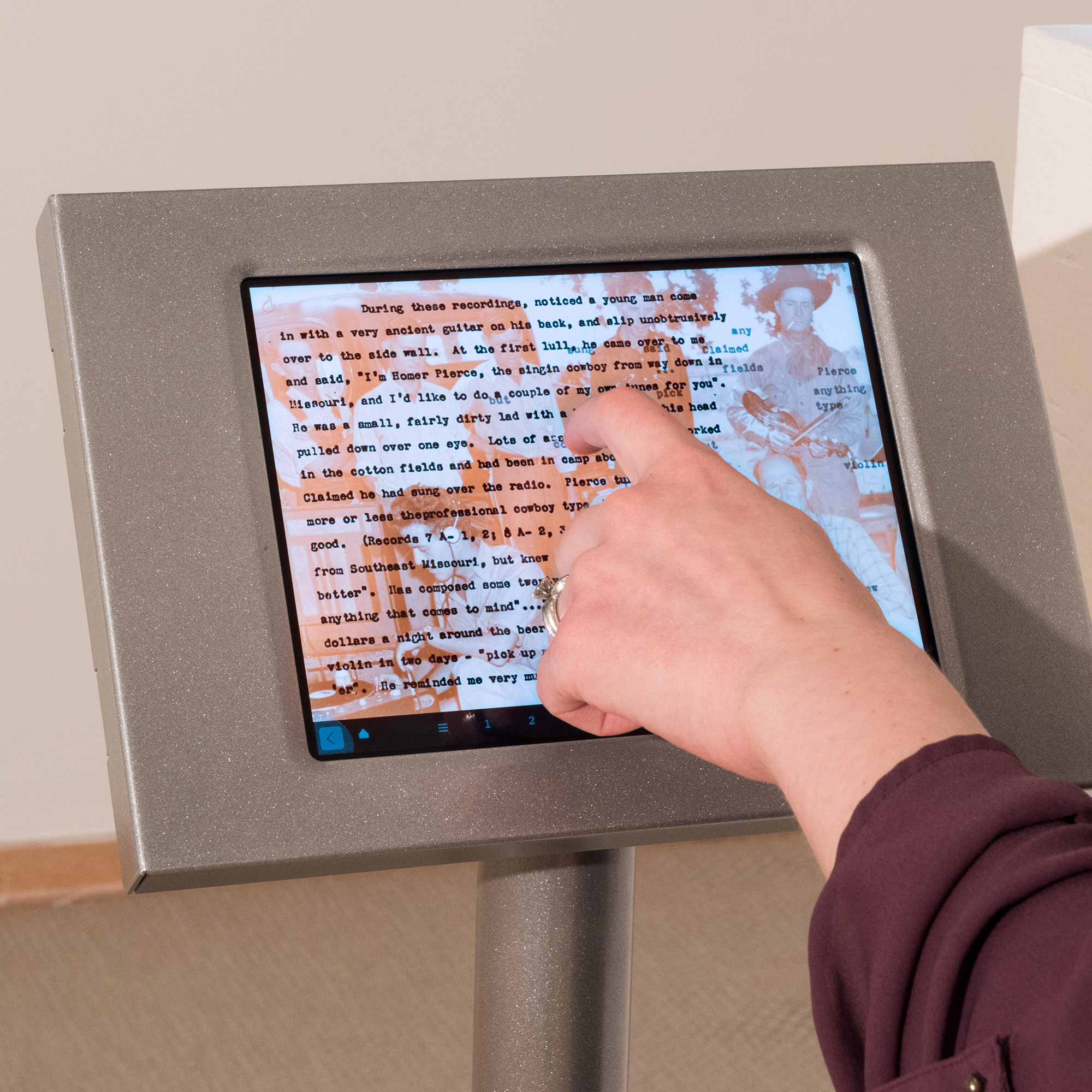 A hand touches an ipad in a stand