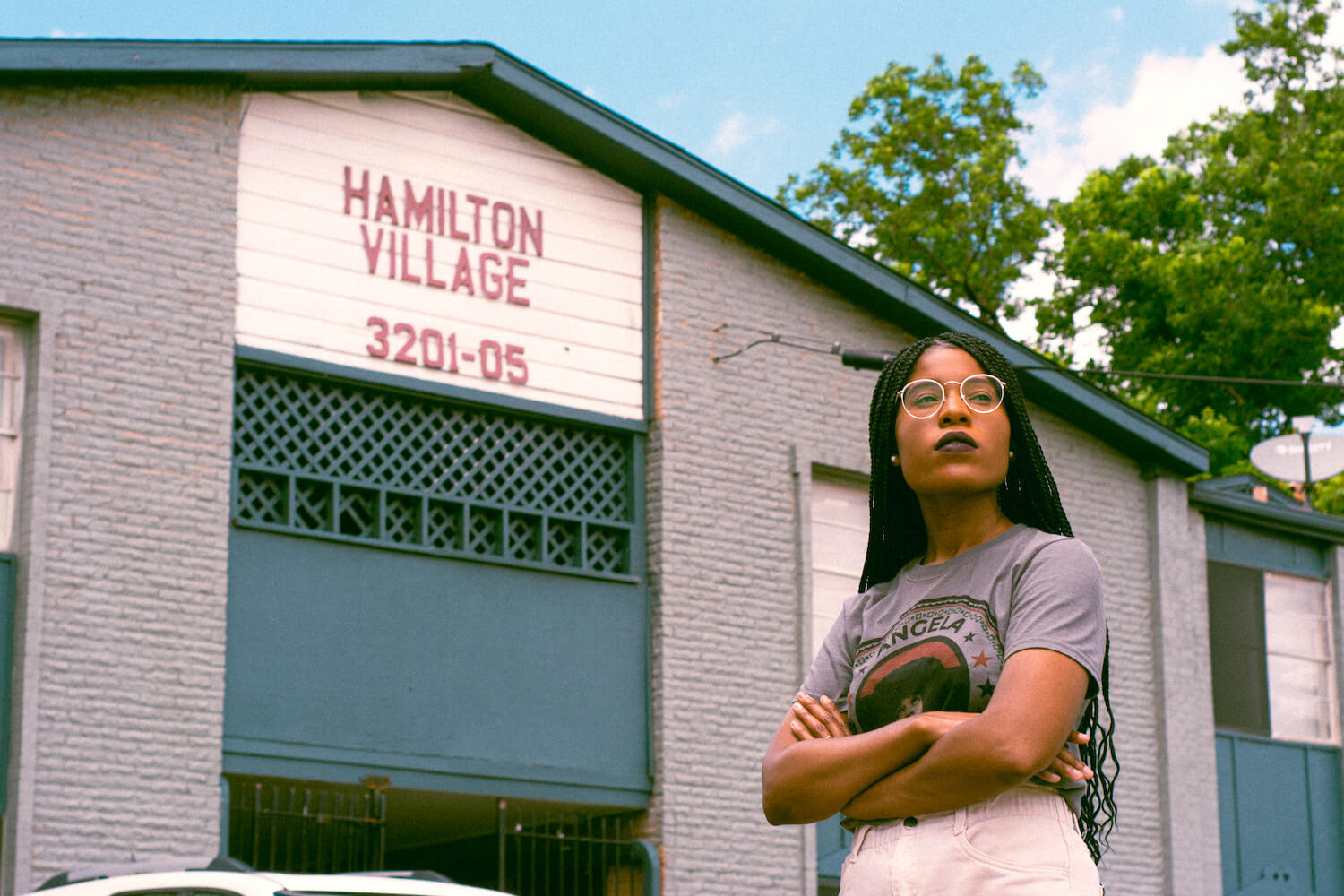 Jessica Mason standing in front of the Hamilton Village Apartment, her childhood apartments.