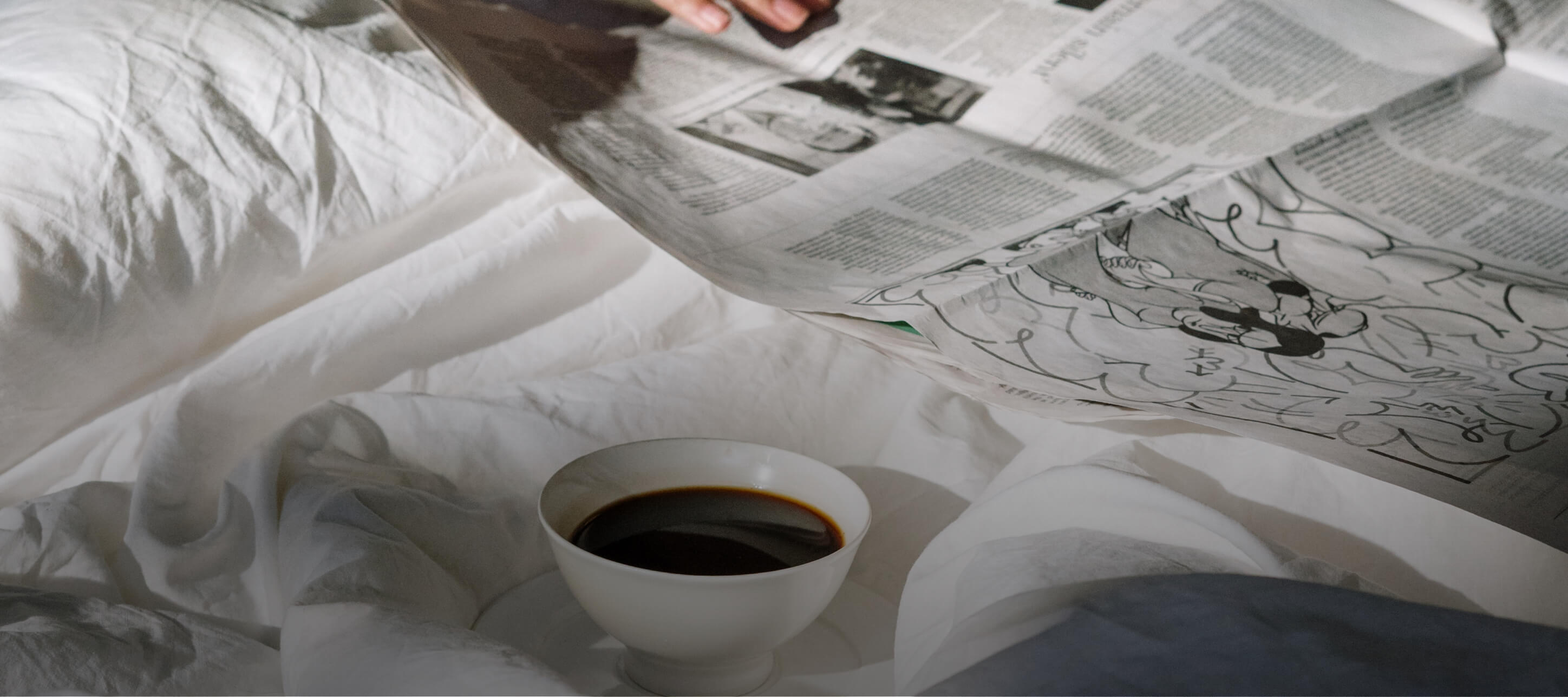 Mood image of reading newspaper in bed with cup of tea.