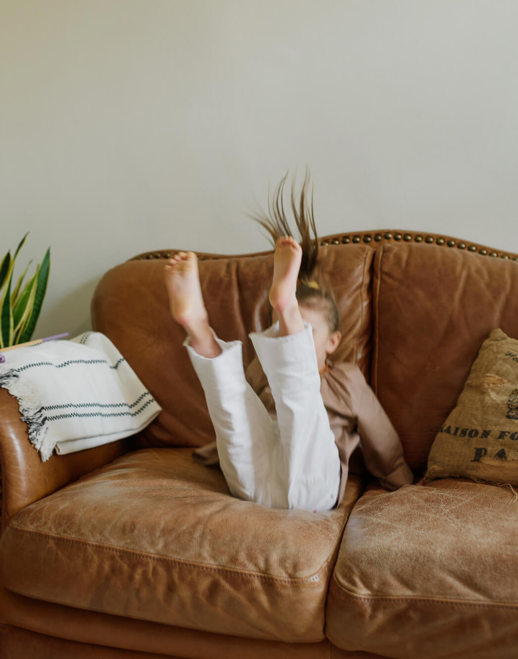 Girl jumping on brown couch.