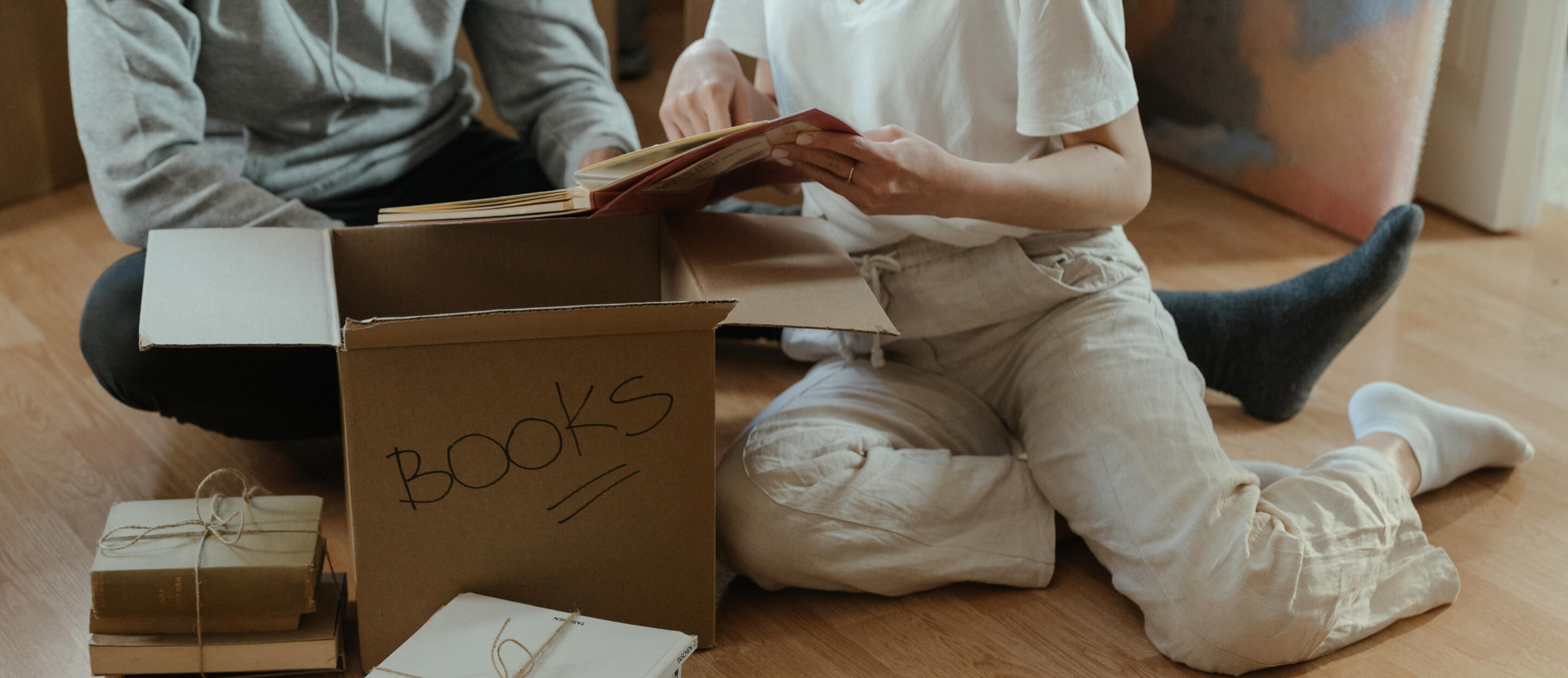"""Couple unpacking paper box labeled as """"Books"""""""
