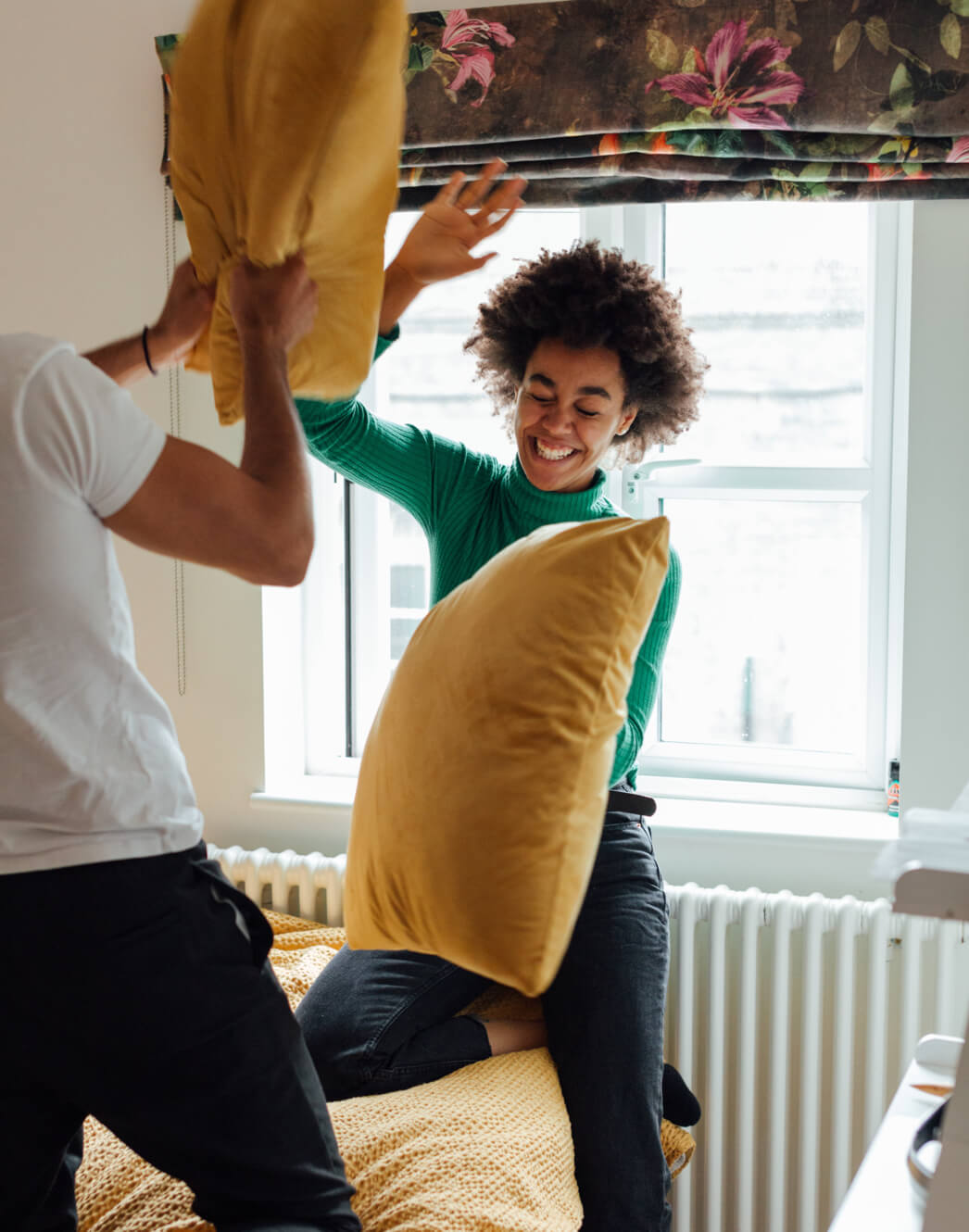 Couple having pillow fight with laugh.