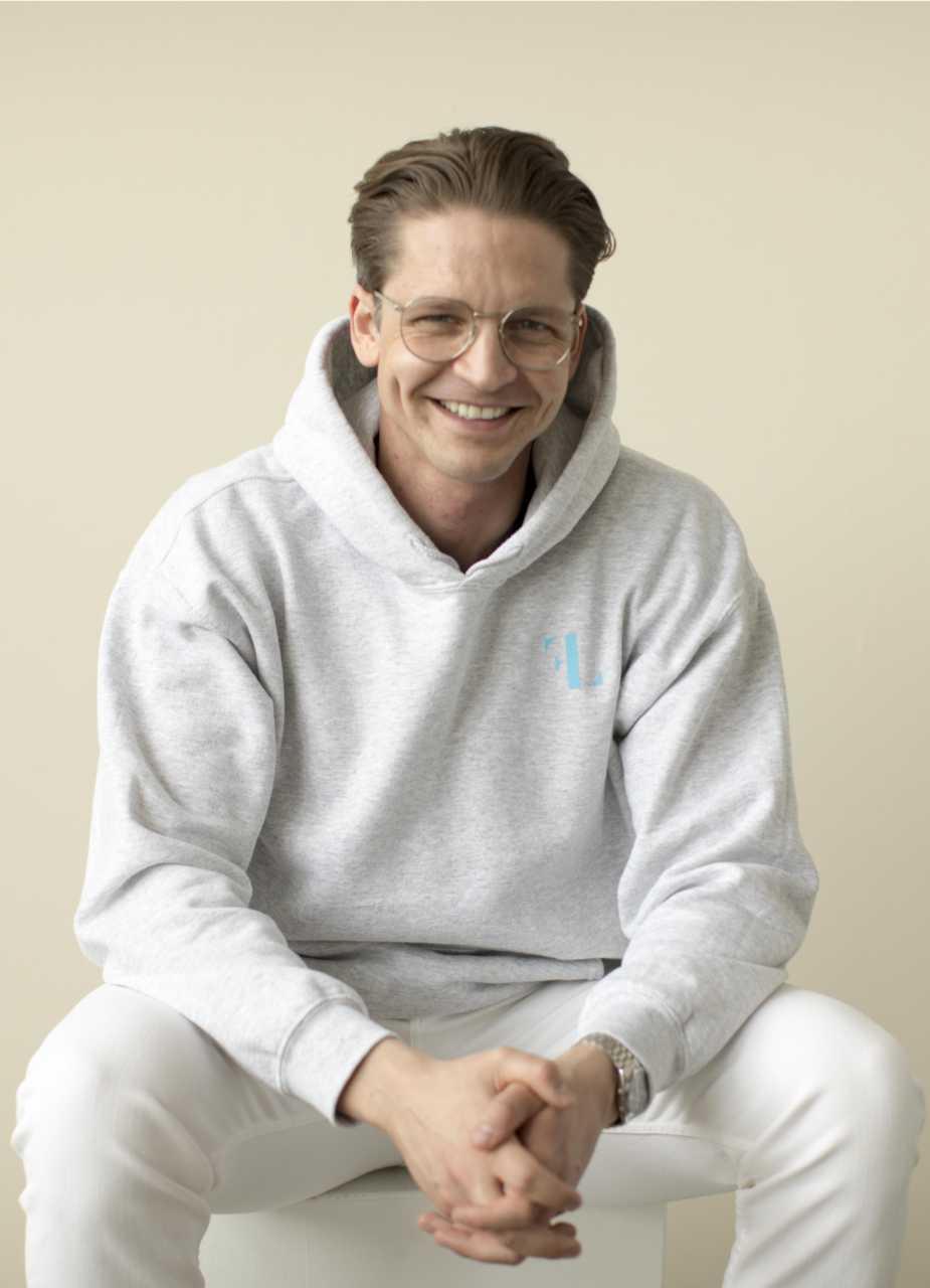 Finn Lorenz mit eigenem Markenhoodie sitzt lachend vor der Kamera