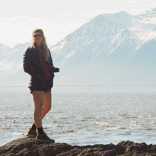 Photo from Instagram of girl standing on rocks in front of mountains