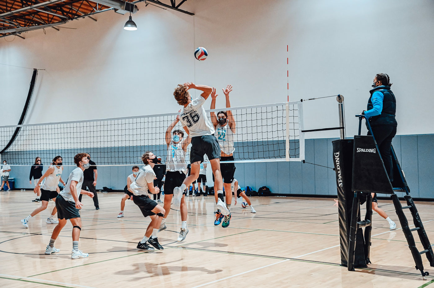 Volleyball player going up for a spike at the net