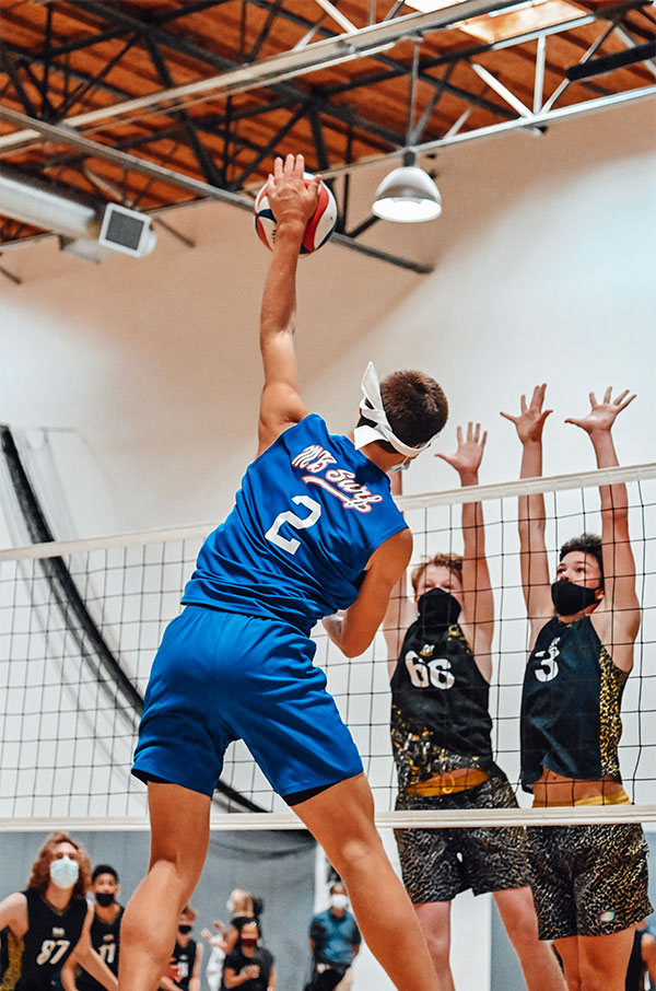 Boy in blue jersey spikes a volleyball, two boys in black jerseys jump to defend on the other side of the net