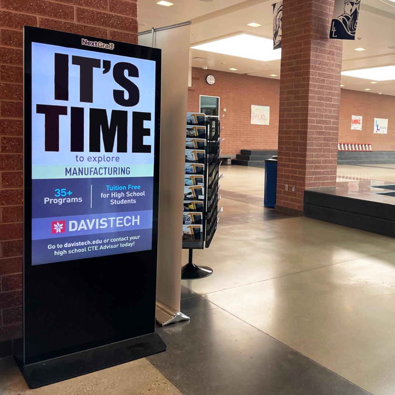 A large digital display in a high school hallway setting