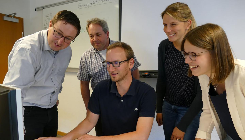 Ein Mitarbeiter erklärt vier Mitarbeitenden etwas am Bildschirm