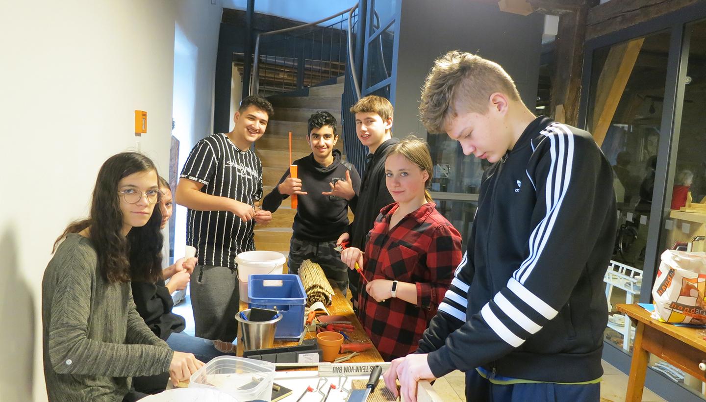 Sieben Jugendliche hantieren an einem Tisch mit Holz, Schilf und Werkzeug
