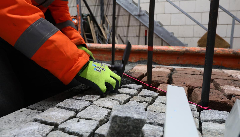 Hände in Arbeitshandschuhen und Arme eines Mitarbeiters, der bei Pflasterarbeiten mit einem Hammer Steine setzt
