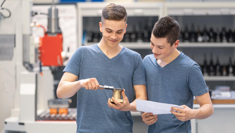 Zwei männliche Auszubildende messen stehend den Durchmesser eines zylindrischen Ventilteils.