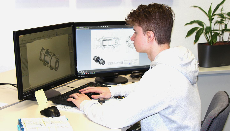 Ein männlicher Auszubildender sitzt am Schreibtisch vor zwei Bildschirmen und betrachtet darauf technische Darstellungen.