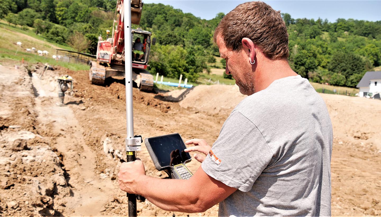 Ein Mann bedient auf der Baustelle ein digitales Gerät mit Touch-Display. Im Hintergrund steht ein Bagger.
