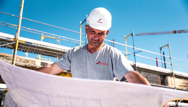 Ein Bauarbeiter mit weißem Helm schaut sich im hellen Sonnenlicht und vor einem Rohbau stehend einen Bauplan an.