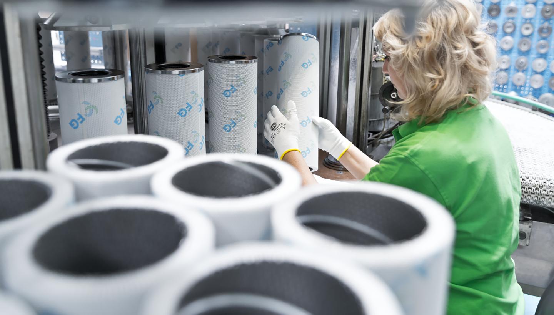 Eine Frau im grünen T-Shirt führt zylindrische Filter einer Maschine zu.