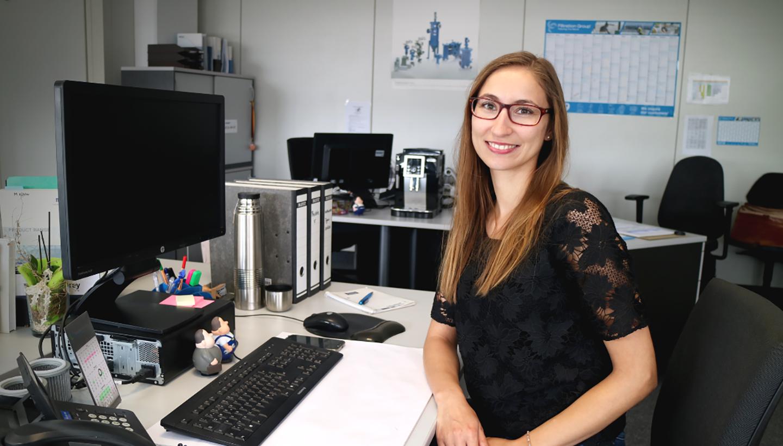 Eine junge Frau sitzt vor ihrem Bildschirm am Schreibtisch und lächelt freundlich in die Kamera.