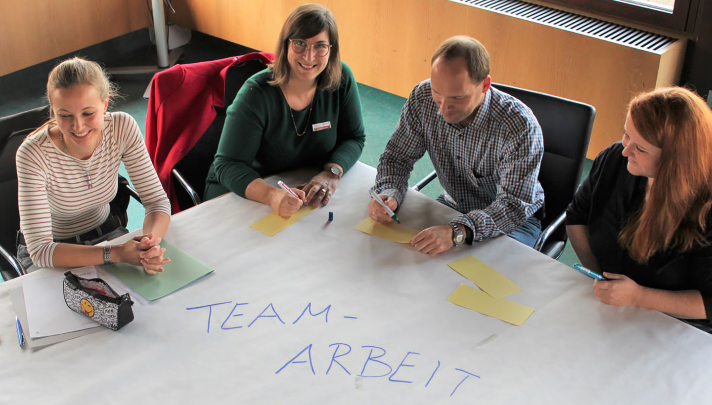 Drei Frauen und ein Mann sitzen, von schräg oben fotografiert, über Eck an einem Tisch, auf dem in Großbuchstaben das Wort Teamarbeit steht.
