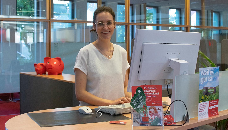 Eine Frau steht hinter dem Sparkassenschalter und lächelt.