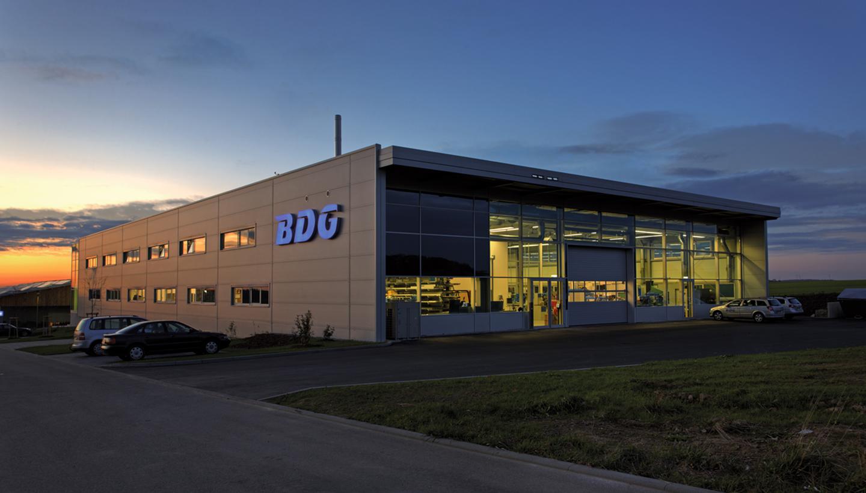 Beleuchtetes Flachdachgebäude mit Glasfront und BDG-Schriftzug in der Abendsonne