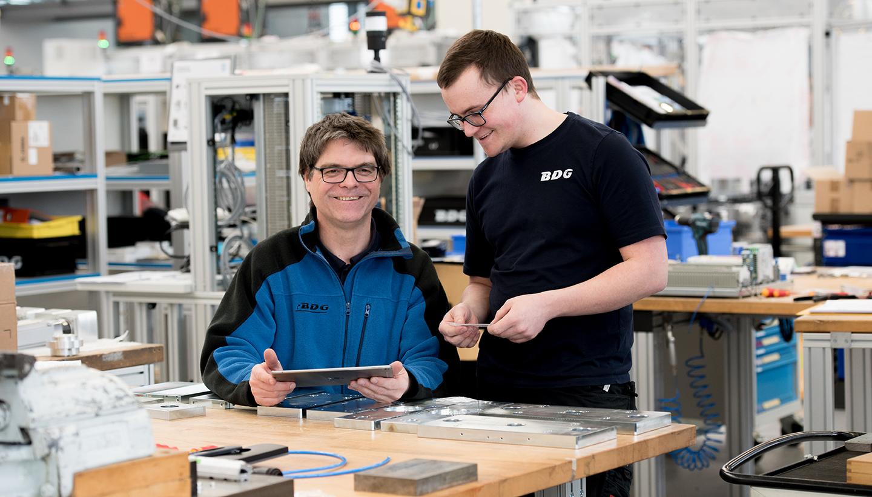 Ein sitzender Mann in BDG-Fließjacke und ein stehender Mann in BDG-T-Shirt an einer Werkbank.